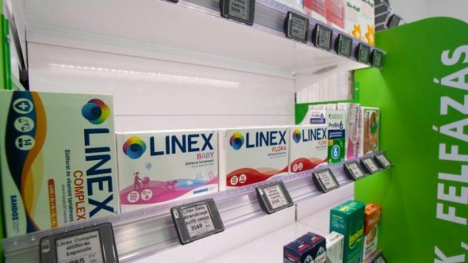 Elektronikus polccímkék patikában, címketartó sínekben a polcokra rögzítve